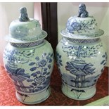 A pair of substantial oriental blue and white vases and covers with painted flowering tree and