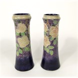 A pair of tall Royal Doulton vases of tapering form with moulded and painted rose and leaf