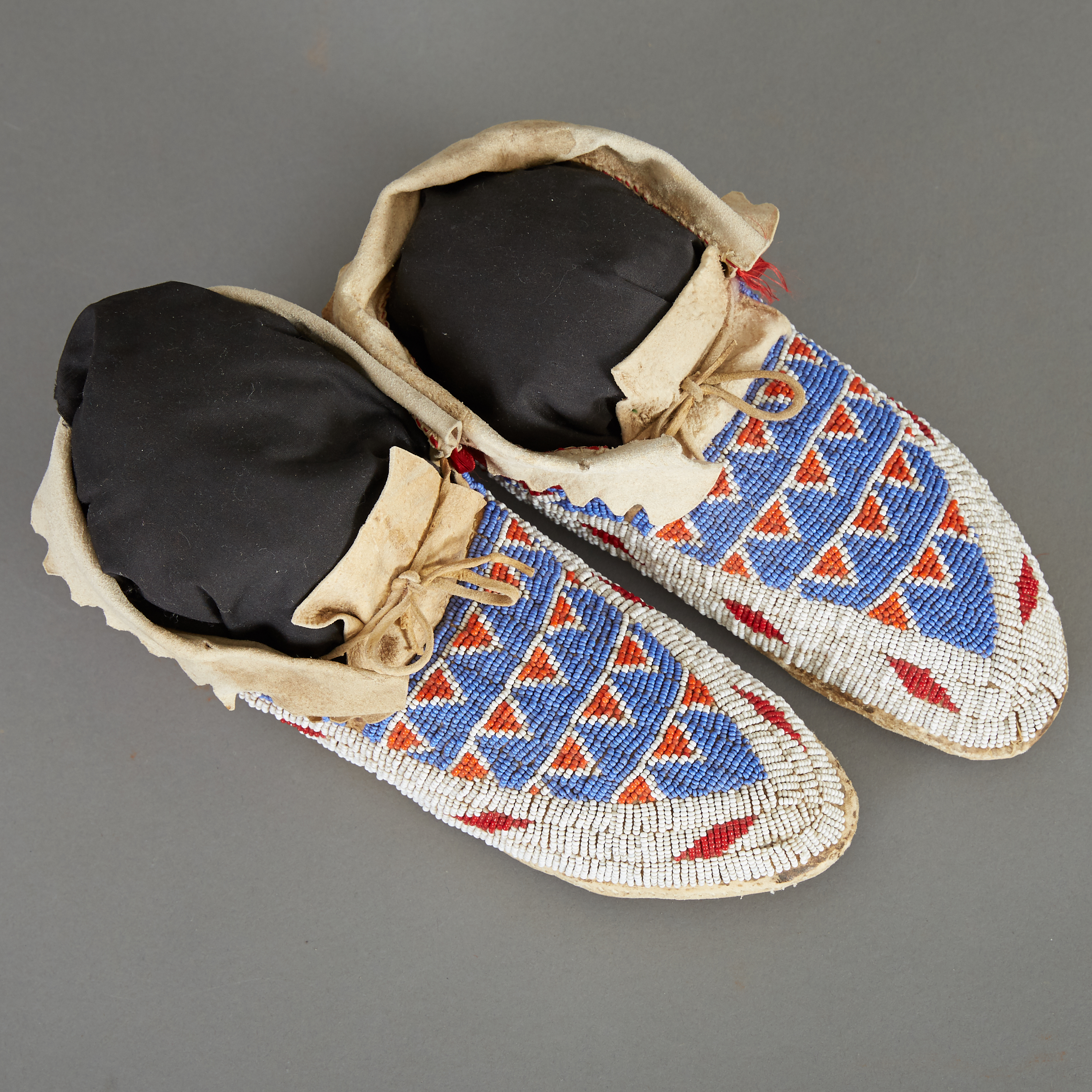 Los 242 - Ute moccasins with geometric beading and fold-over ankle cuffs, southern Colorado, circa 1910....