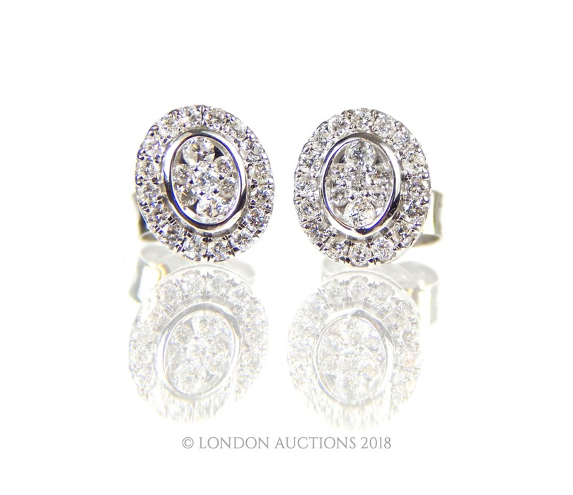 Lot 21 - A Pair of White Gold and Diamond Stud Earrings.