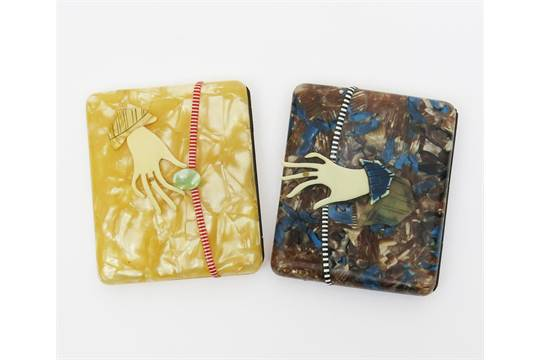 Lot 780 - Two French hand-clasp celluloid cigarette cases,  one marbled cream, with yellow sleeved ivorine