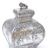 A 19th century French silver tea caddy, of rectangular baluster form, with relief embossed lover