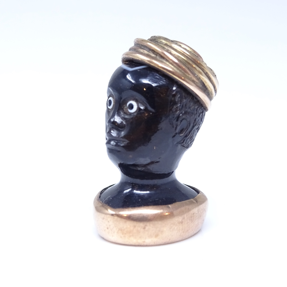 A 19th century banded agate figural Blackamoor seal fob, unmarked rose gold mounts with cabochon