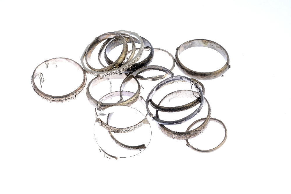 Lot 11 - A selection of silver and white metal bangles. To include three silver hinge bangles one of textured