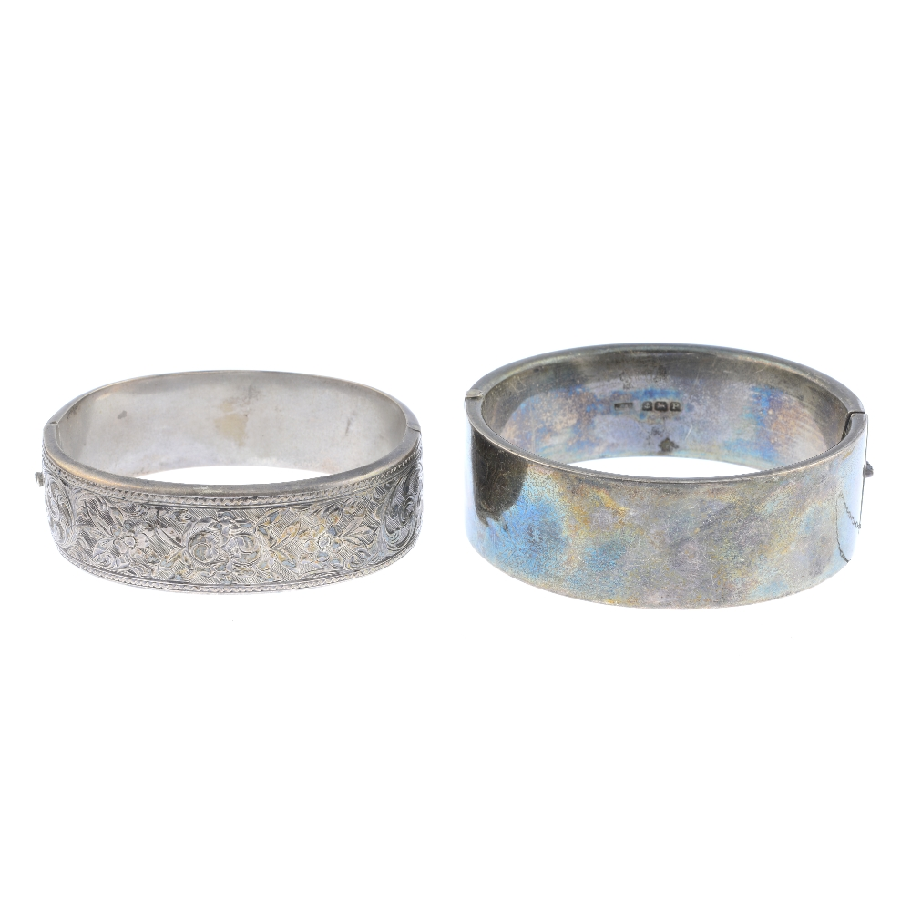 Lot 32 - Four bangles. To include an early 20th century silver foliate engraved bangle, a monogram engraved