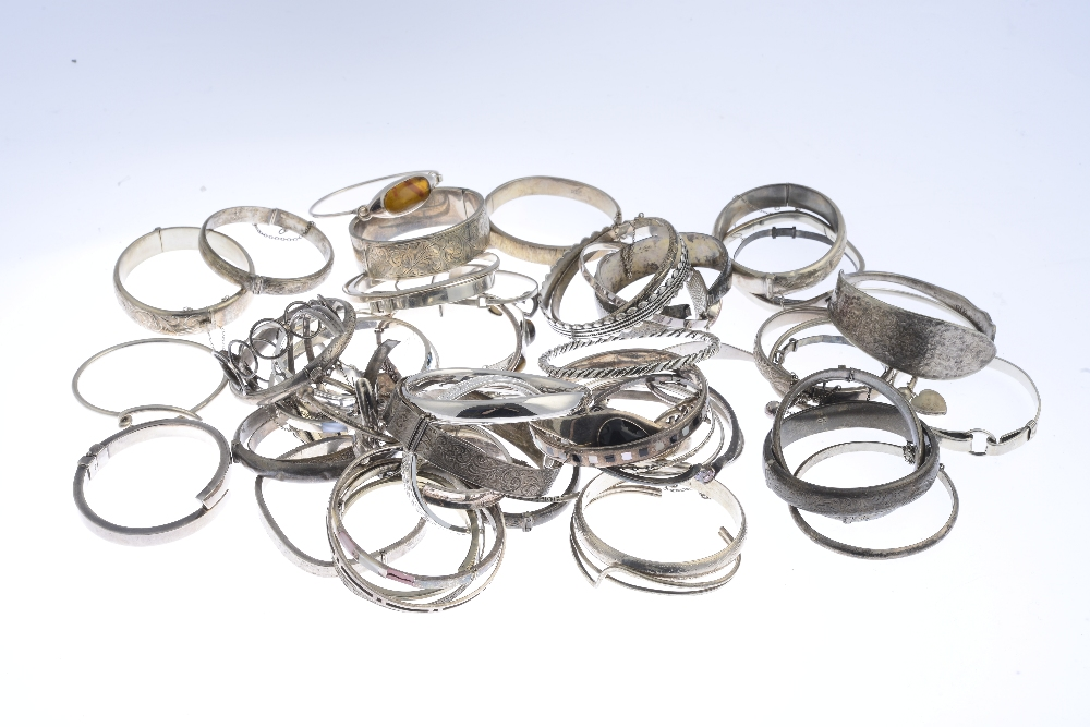 Lot 59 - A selection of silver and white metal bangles. To include two silver twisted wire bangles with marks