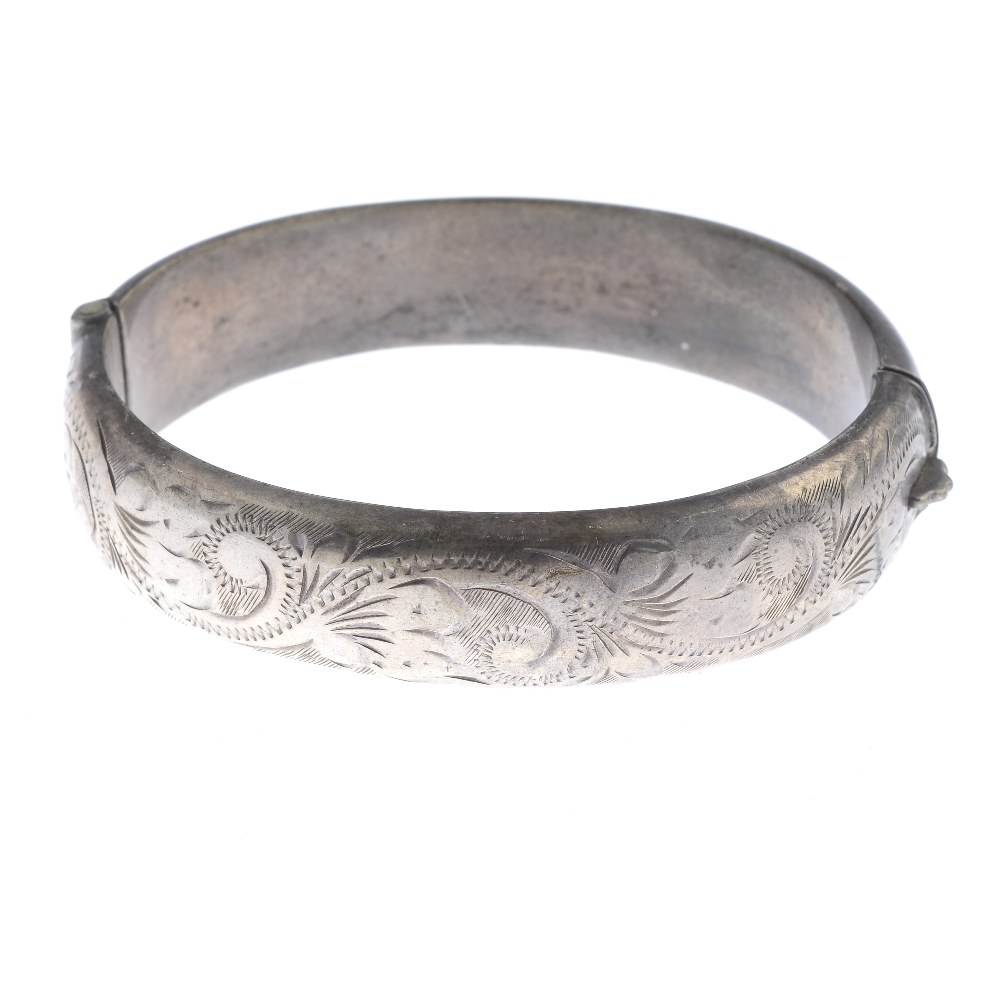 Lot 58 - A selection of silver and white metal bangles. To include a silver hinge bangle with engraved detail