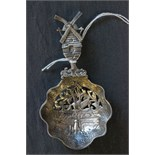Lot 9 - A 19th century Dutch silver tea strainer, decorated with a bird in flight to the bowl, with windmill