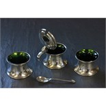 Lot 49 - A three piece silver cruet set, with green glass liner and matching spoon, Birmingham 1910