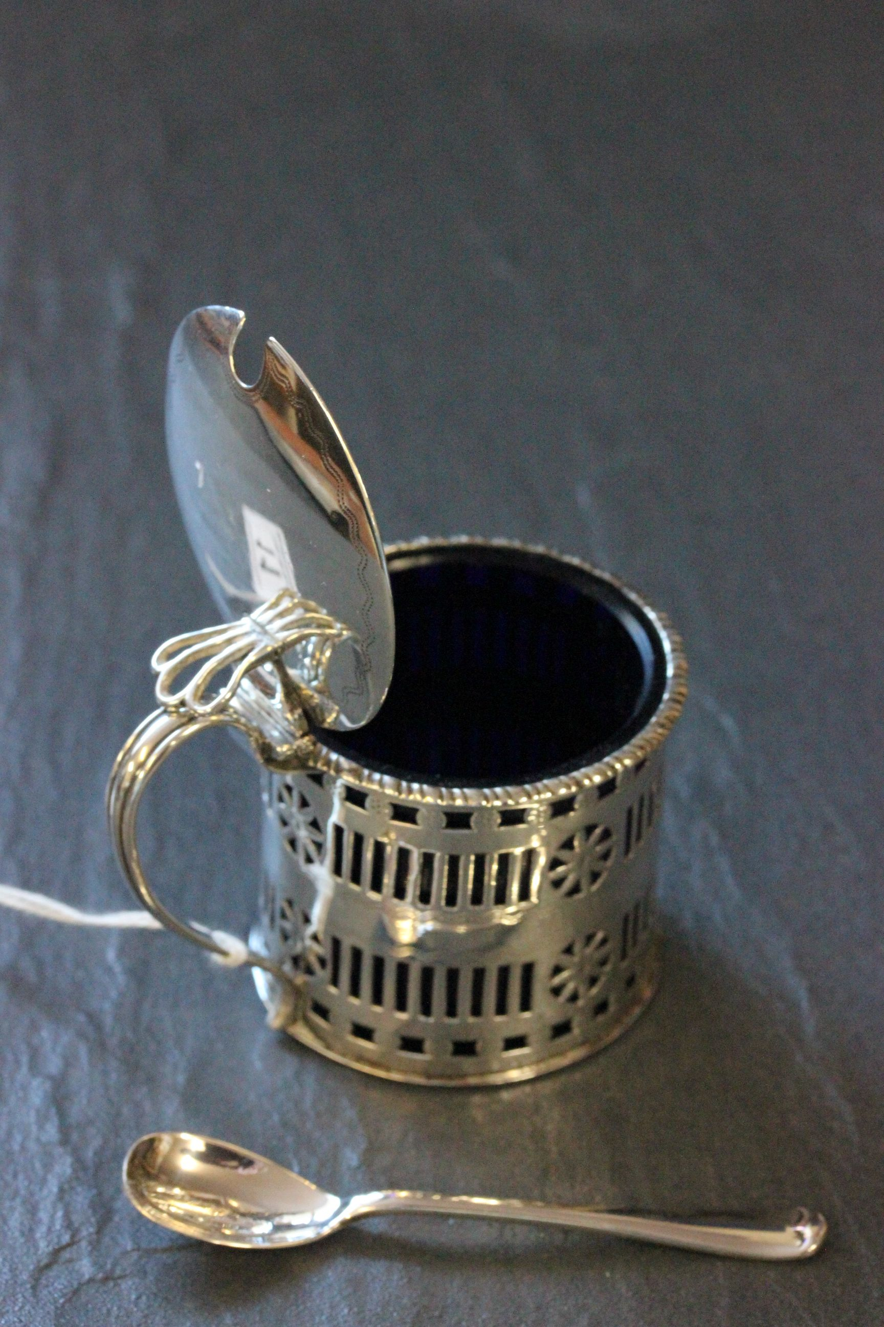Lot 11 - A silver mustard pot, with blue liner, Birmingham 1913, along with a silver mustard spoon 1907,