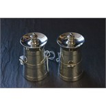 Lot 13 - A pair of silver novelty pepperettes, each in the form of milk churns with carry fixed handles, each