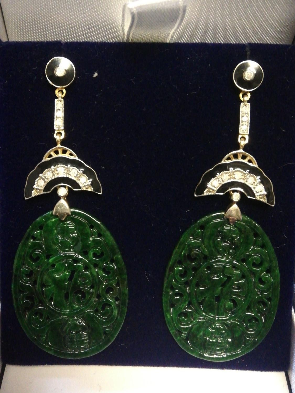 Pair of silver & gold drop earrings set with large oval patterned jade, diamonds & black enamel