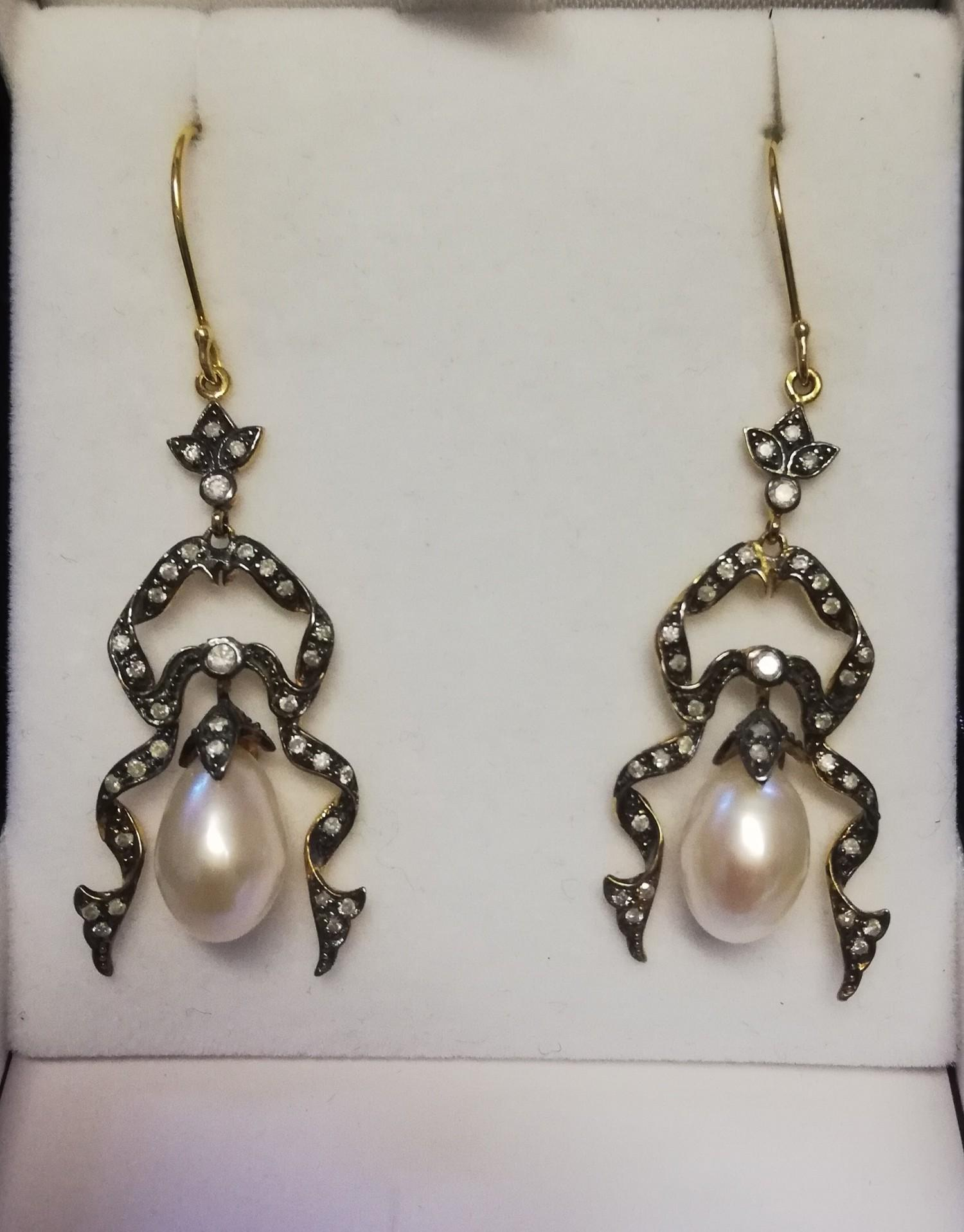 Pair of ornate drop earrings set with diamonds and a suspended pearl
