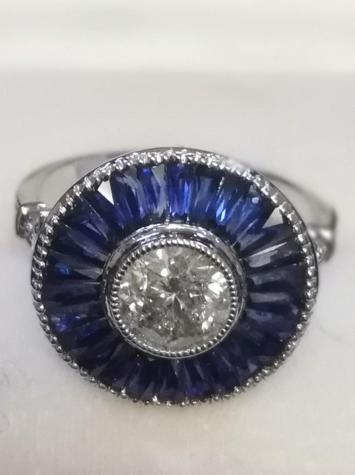 Large platinum target style ring set with central diamond and calibre cut sapphires