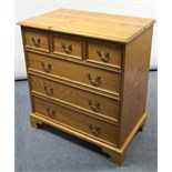 Lot 1 - A pine chest fitted three short & three long graduated drawers with brass swing handles, & on