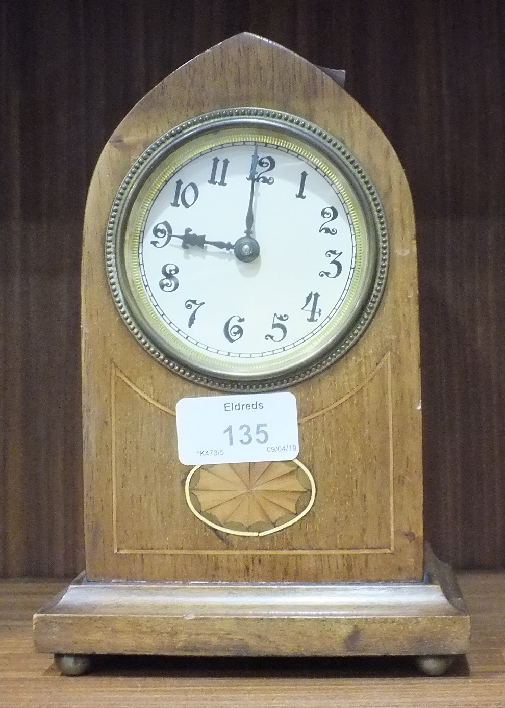 Lot 135 - An Edwardian inlaid mahogany lancet shaped mantel clock, 20cm high and a brass standard lamp in