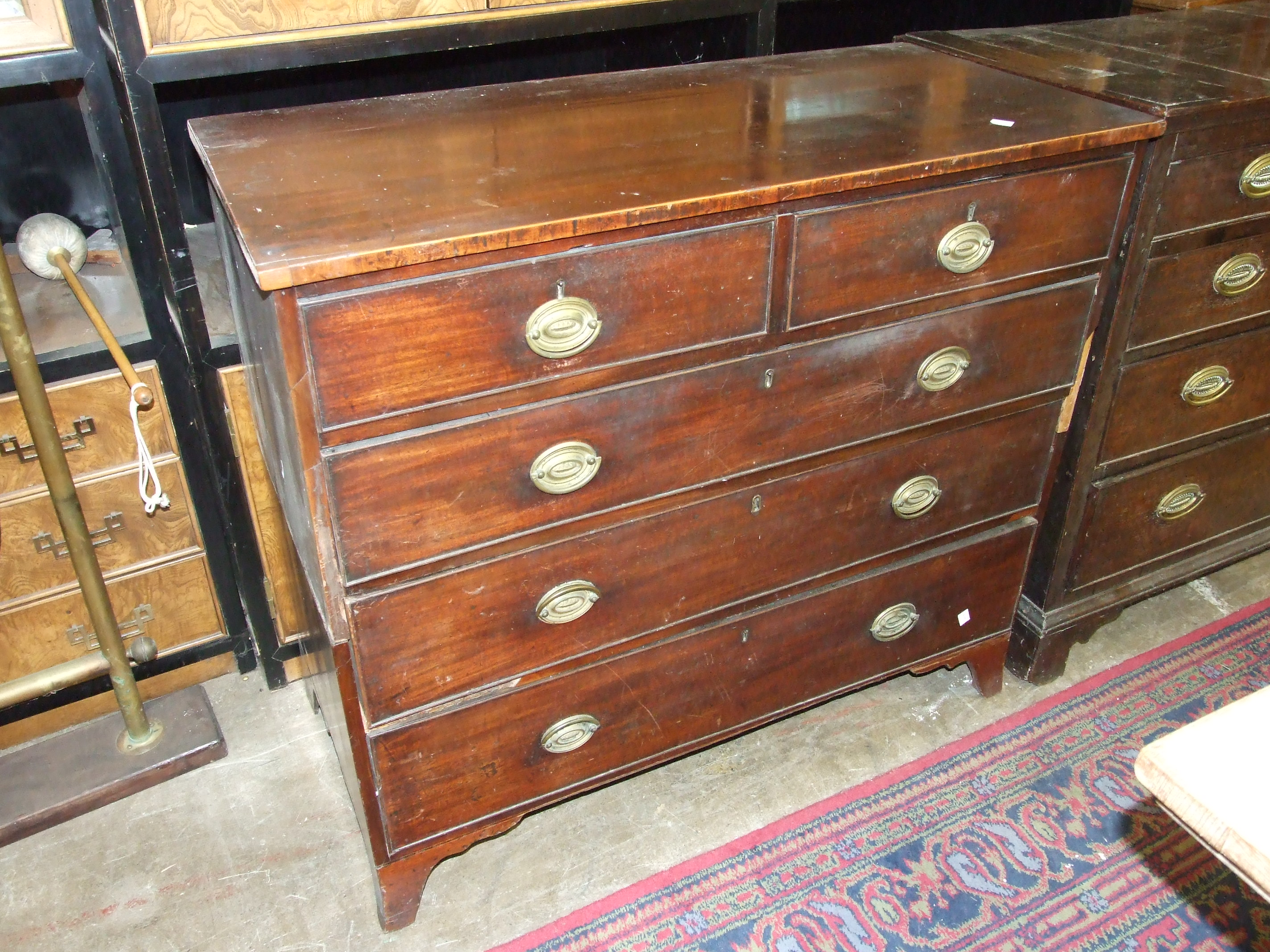 Lot 13 - A Georgian mahogany chest of two short and three long cockbeaded drawers on bracket feet, in two