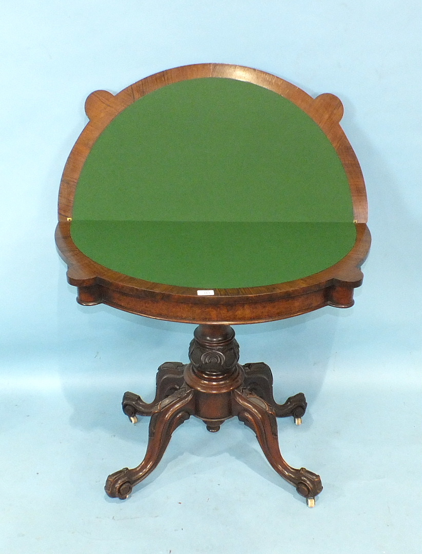 Lot 21 - A Victorian walnut fold-over card table, the shaped top with carved border, on turned and carved