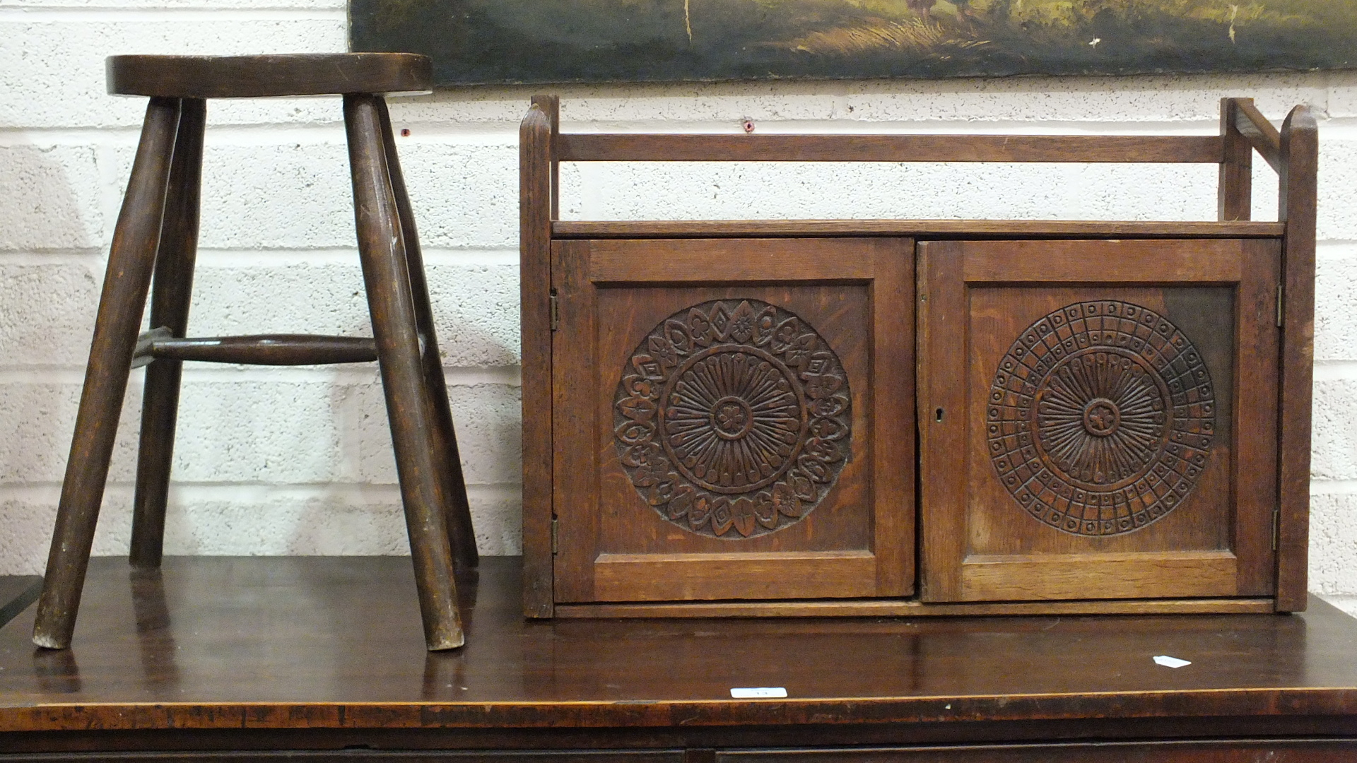 Lot 38 - An Edwardian oak two-door medicine cabinet, 63.5cm wide, 42cm high and a stool, (2).