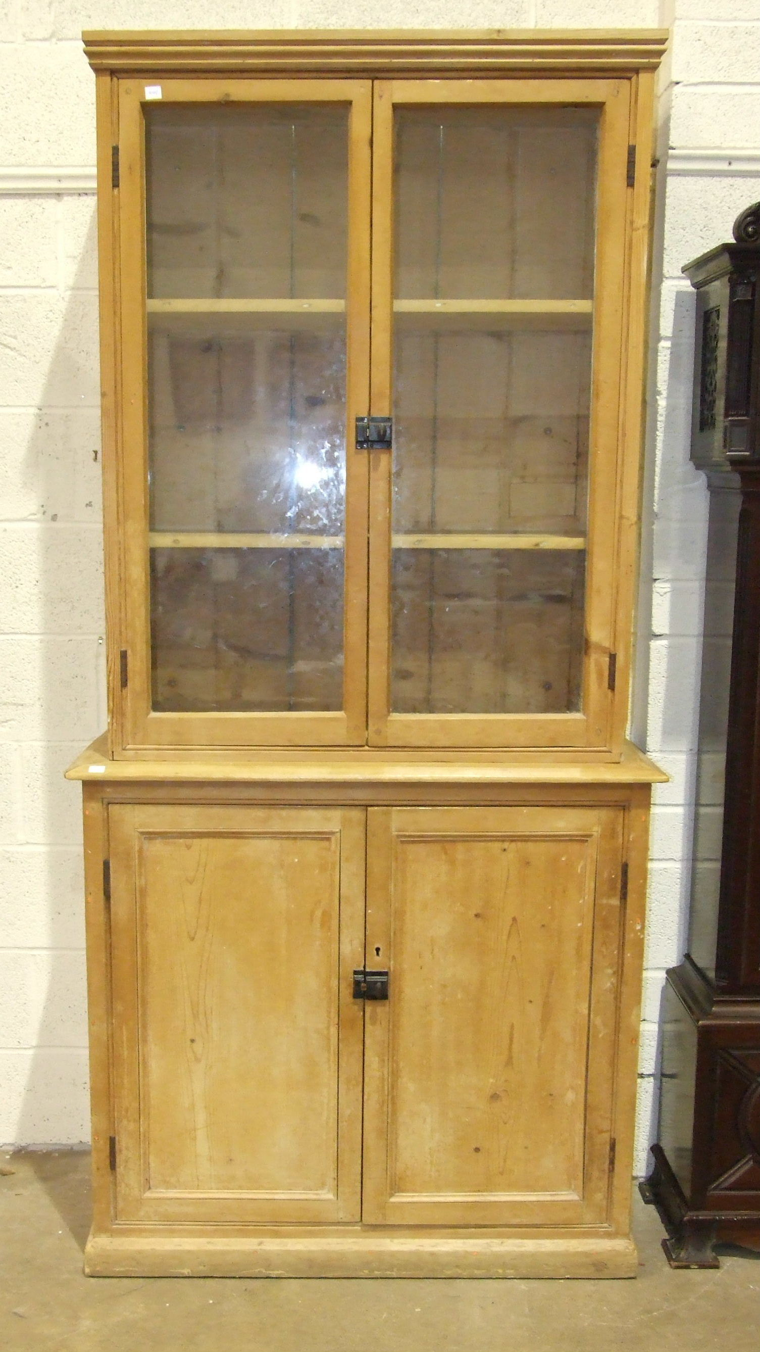 Lot 2 - A pine dresser, the upper section fitted with a pair of glazed doors above a two-door base, 95cm