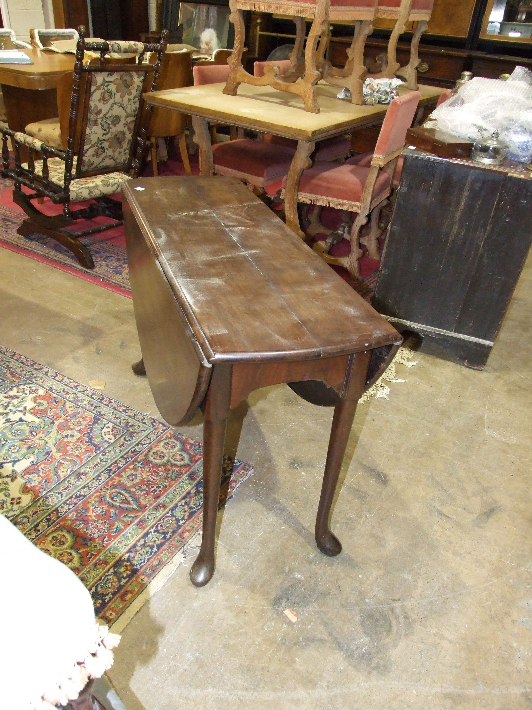 Lot 16 - An 18th century Cuban mahogany oval drop-leaf dining table on turned legs with pad feet, 17 x
