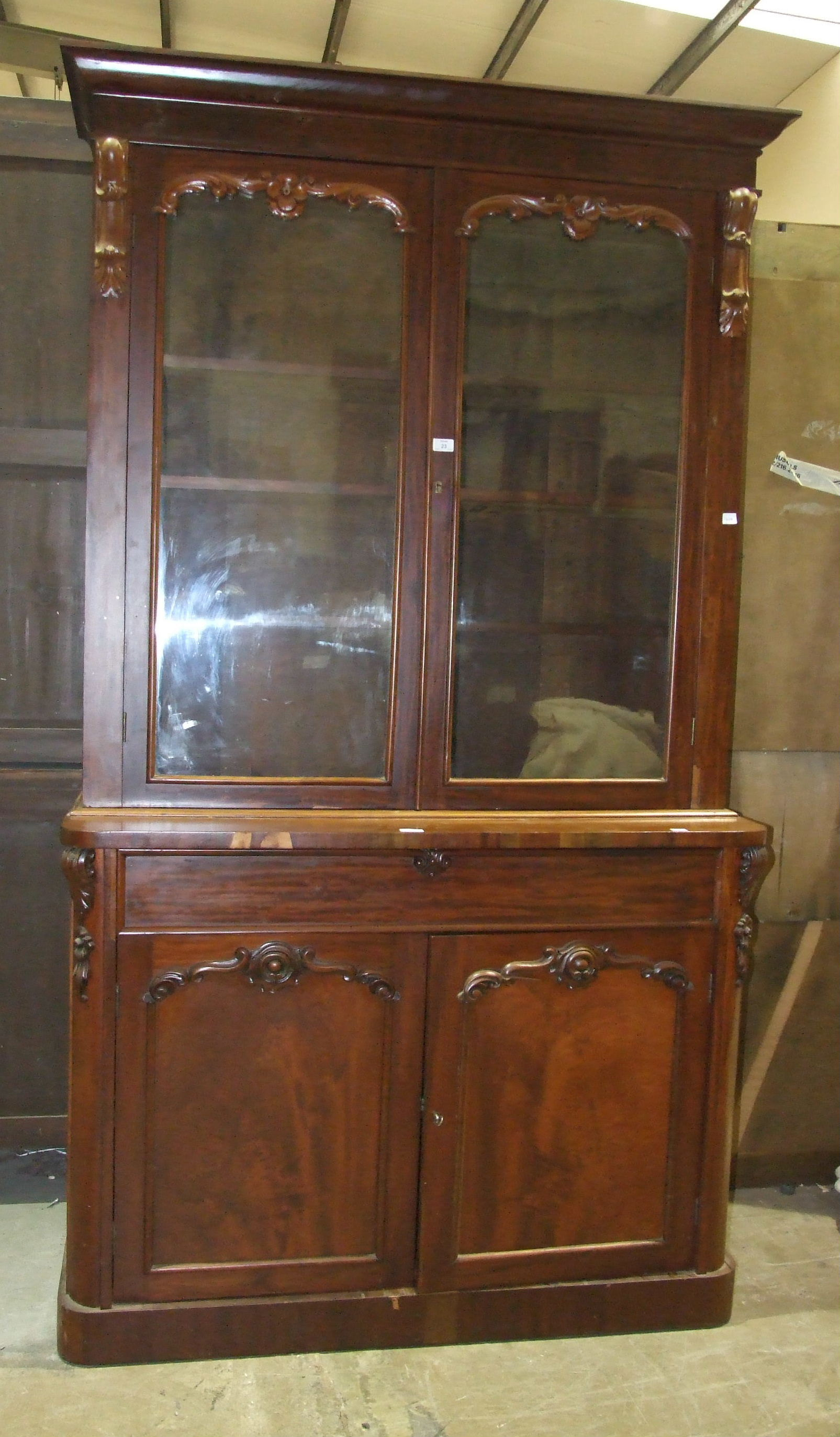 Lot 23 - A Victorian mahogany bookcase, the cornice above a pair of glazed doors, a drawer and cupboard