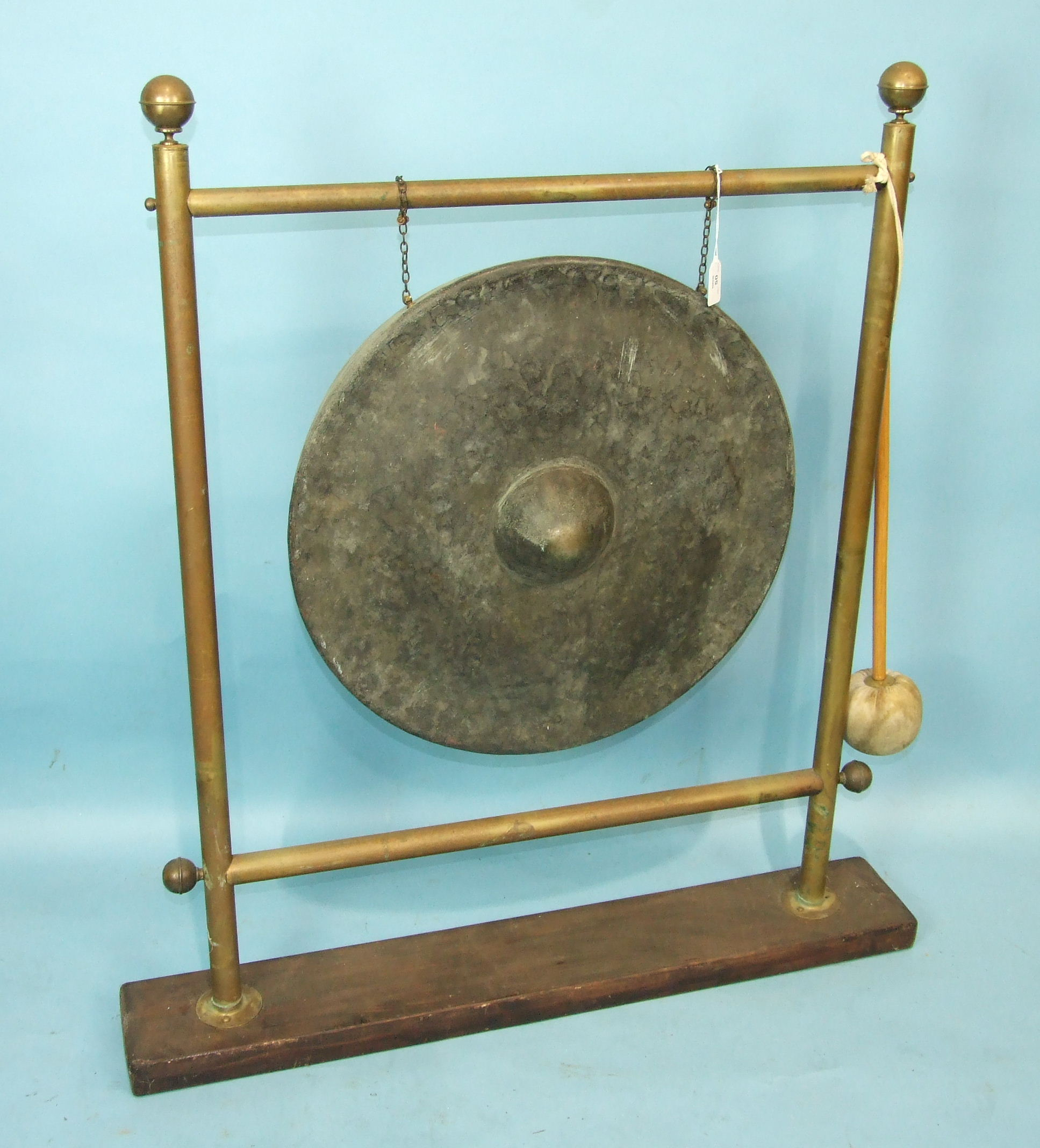 Lot 14 - A circular bronze gong with central raised boss on later brass stand with beater, gong 55cm