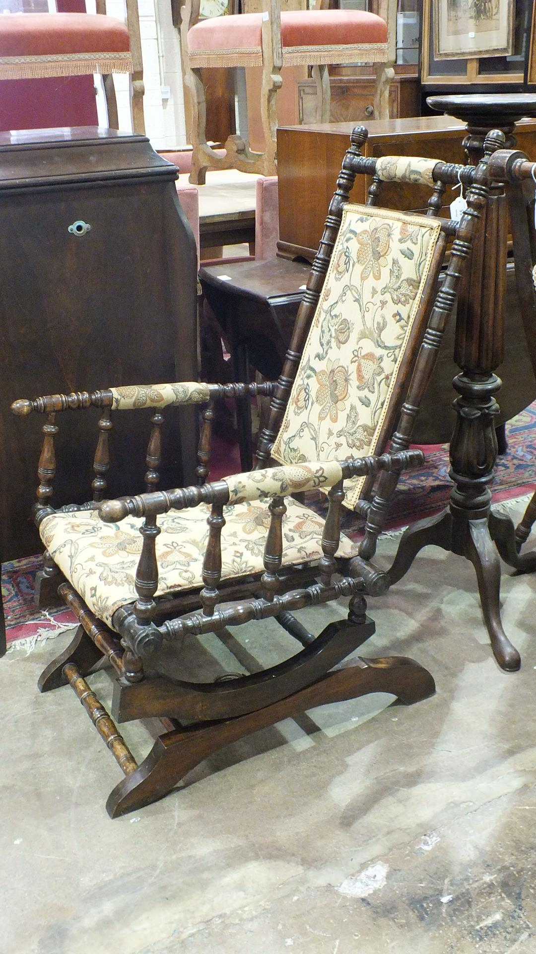Lot 55 - A stained and turned wood American style rocking chair with floral padded back and seat.