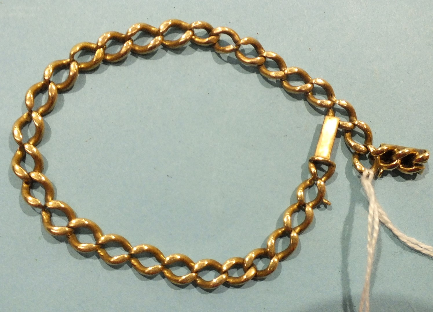 Lot 191 - A gold curb link bracelet with concealed clasp, (unmarked, tested as 14ct, worn), 16g.