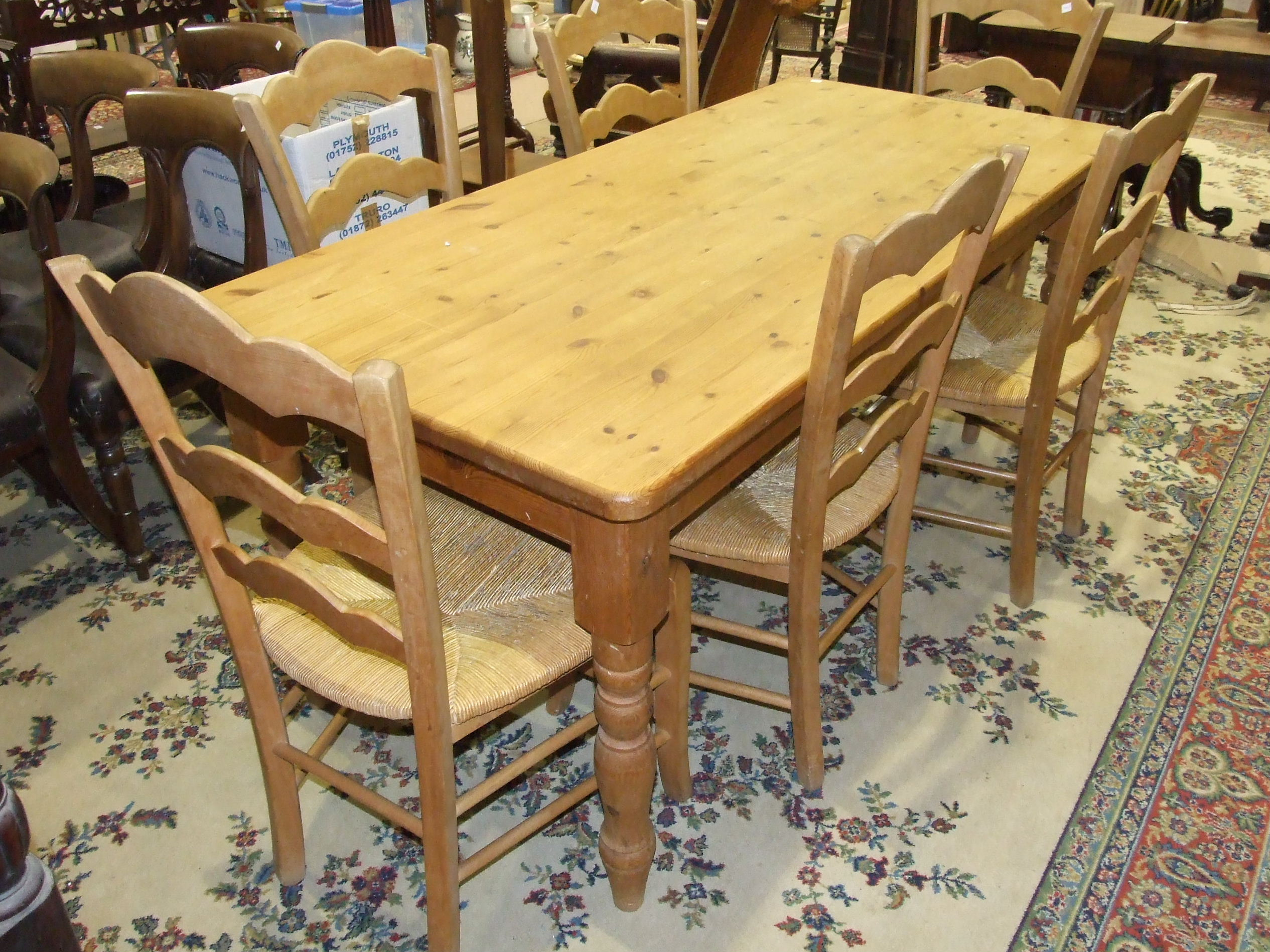 Lot 1 - A modern pine rectangular kitchen table on turned legs, 181 x 85cm, together with a set of six
