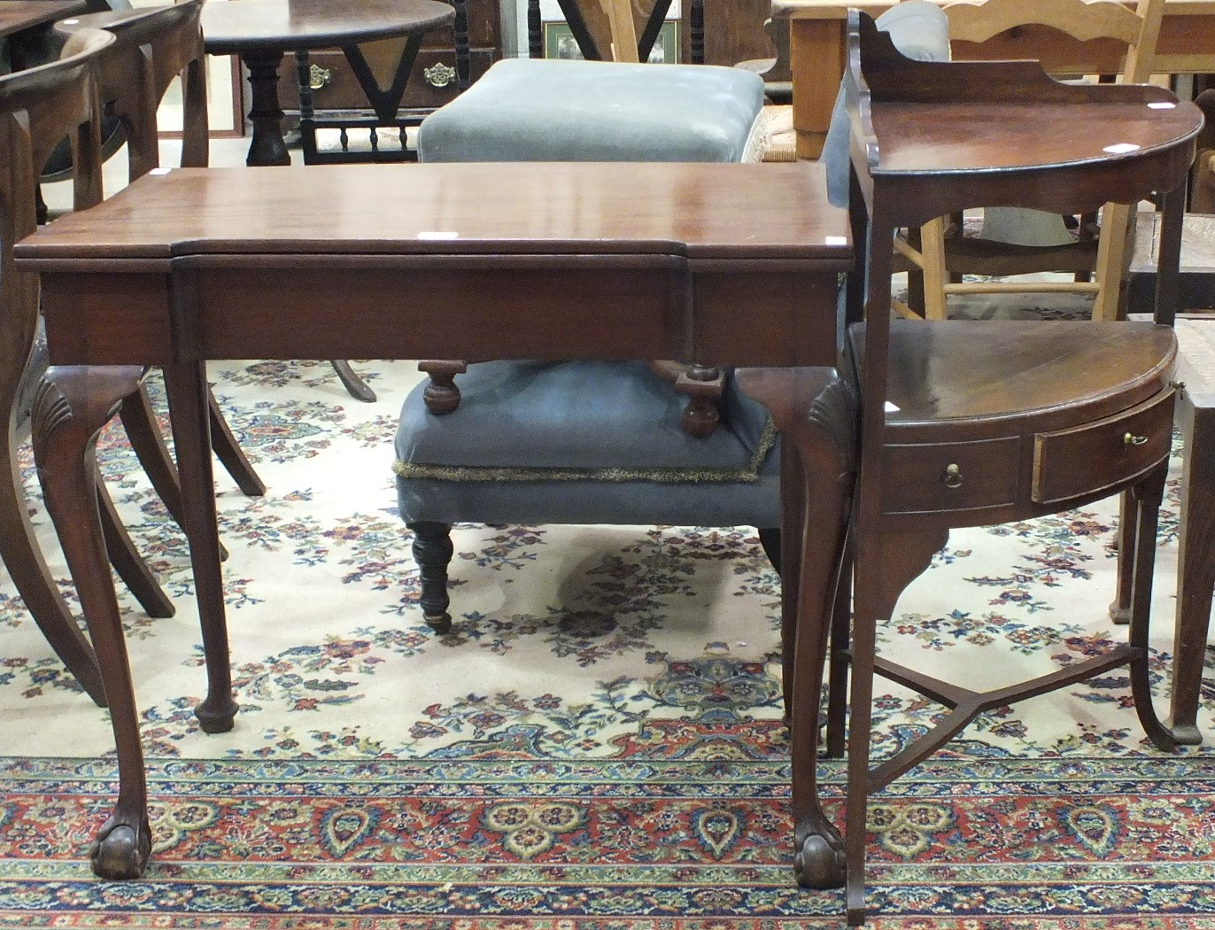 Lot 56 - A mahogany carved fold-over card table, 86cm wide and a mahogany two-tier corner unit, (20