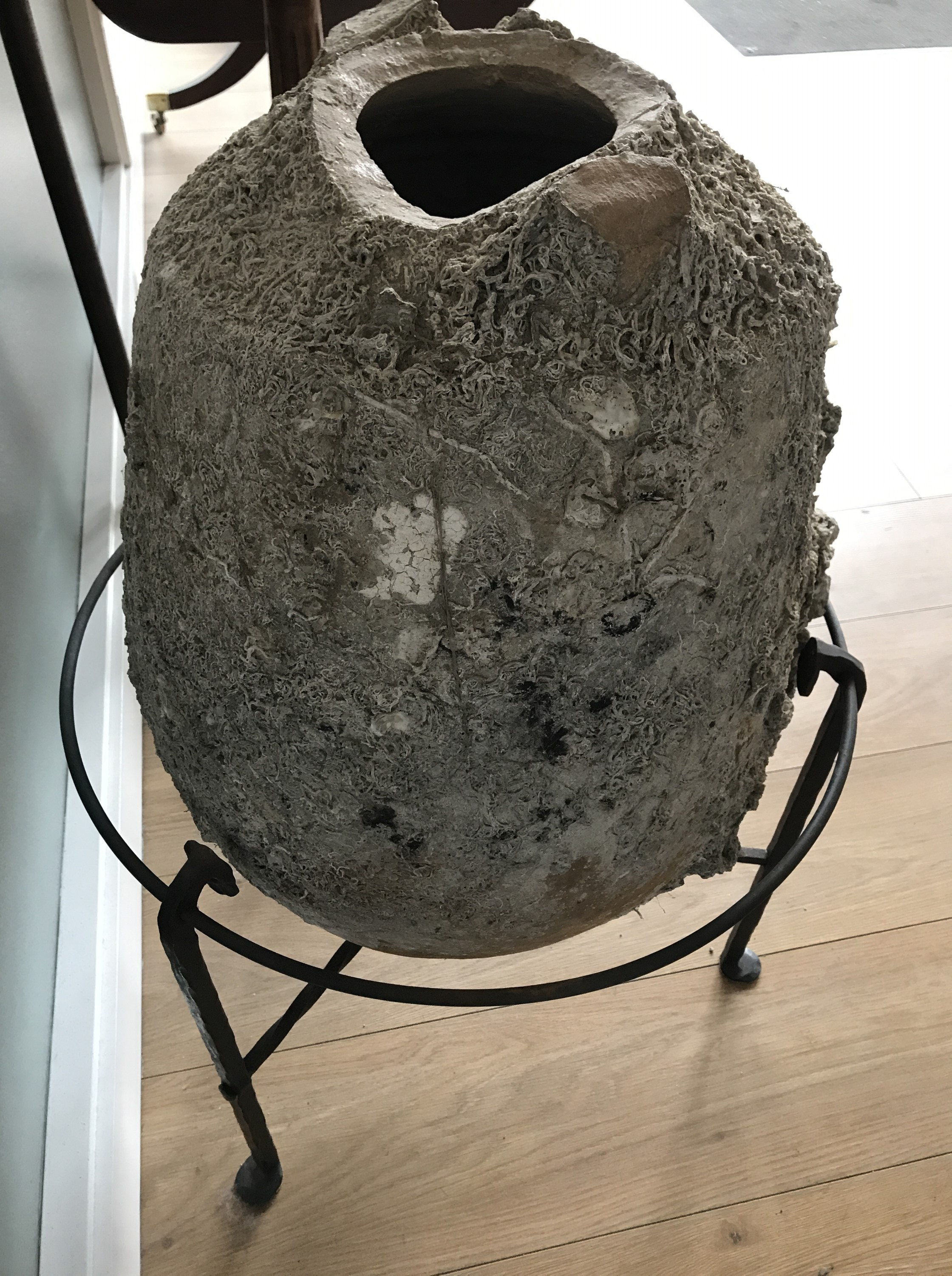 Lot 12 - A classical Graeco-Roman amphora, wreck-recovered and encrusted, on wrought-iron stand, 75 cm