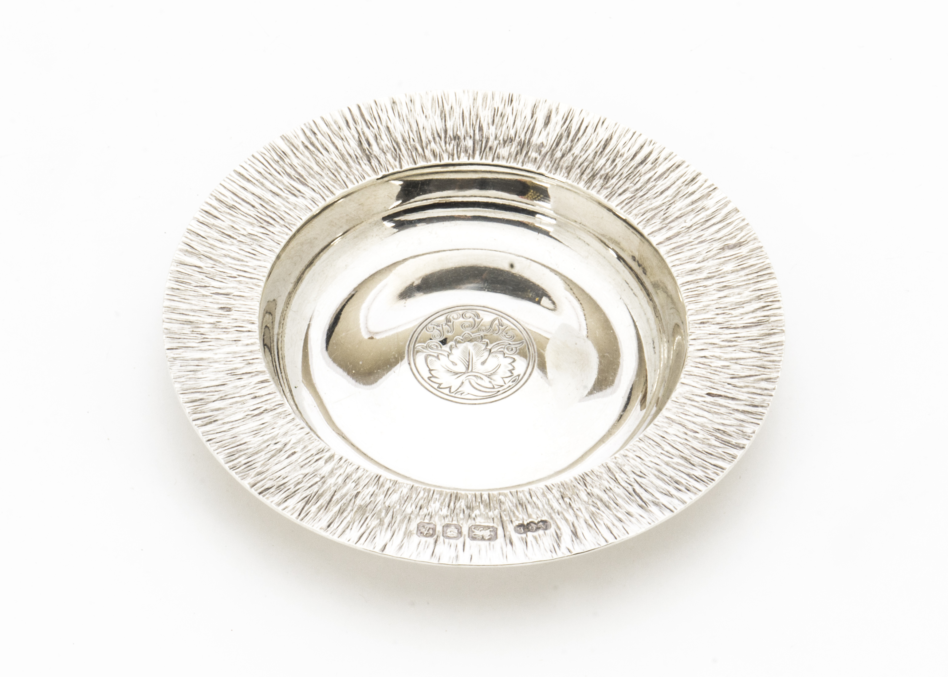 Lot 59 - A 1970s silver dish by Gerald Benney, circular having bark effect textured rim and engraved grape