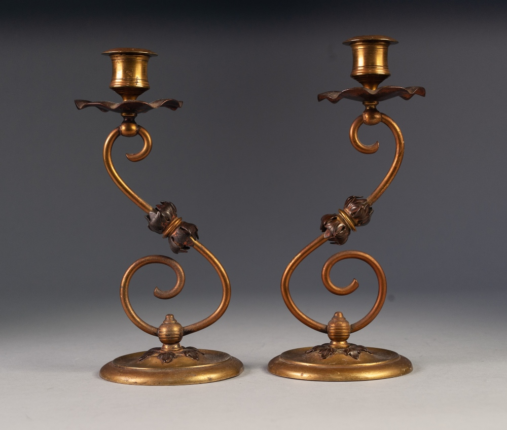 Lot 42 - PAIR OF ARTS AND CRAFTS BRASS AND COPPER CANDLESTICKS, each of 'S' scroll form with urn shaped