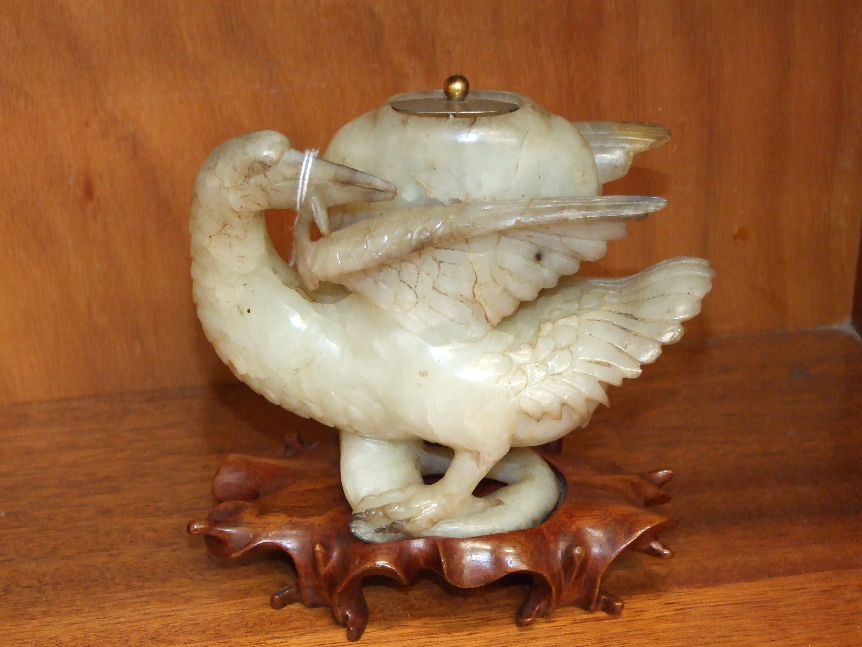 Lot 246 - A jade-type hardstone model of a bird supporting a beaten white metal lidded stone pot between its