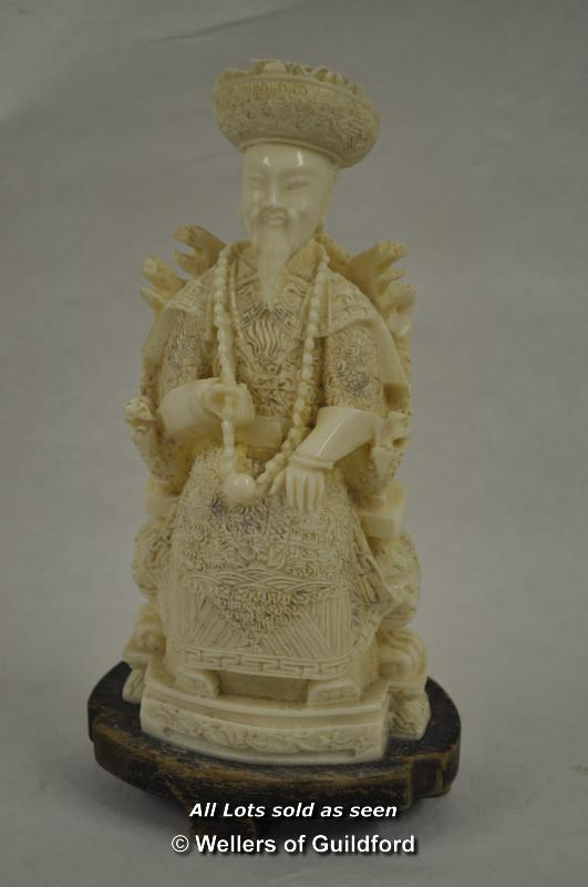 Lot 7282 - A resin figure of a Chinese dignitary on a throne, wooden stand, 22cm.