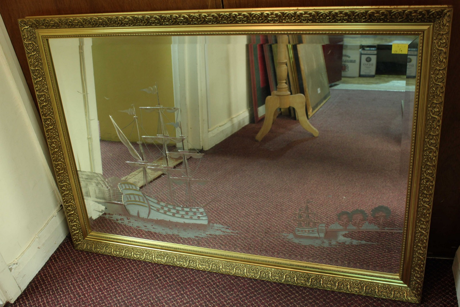 A large gilt framed wall mirror, engraved with a maritime scene of a ...