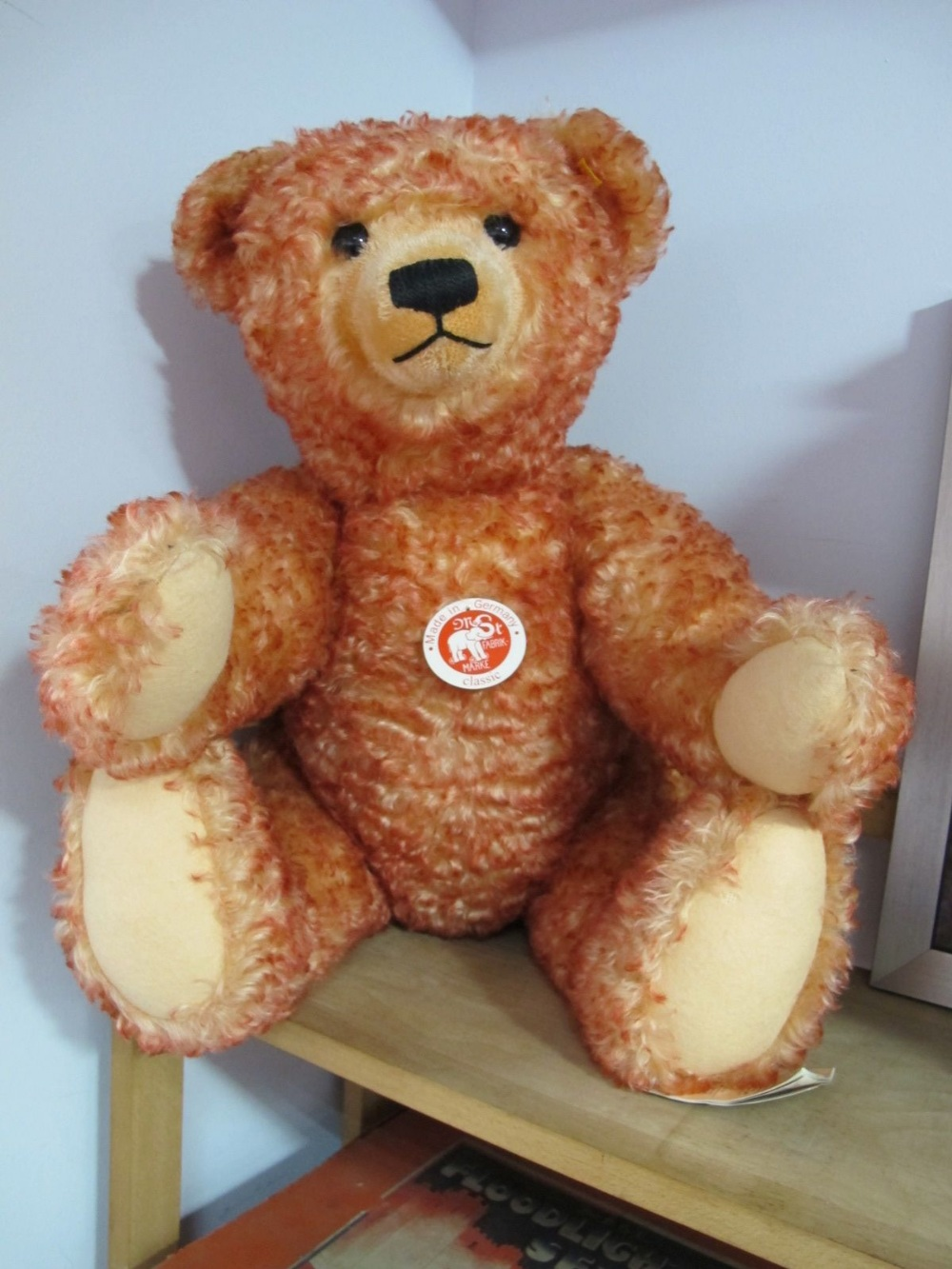 Lot 48 - A Modern Steiff Classic Teddy Bear 'Sitting Down', red, with tags, 000218. Small hole noted on the