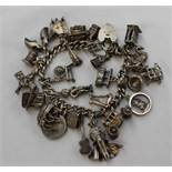 A silver charm bracelet set with numerous charms including a telephone, violin, blackboard, clogs,