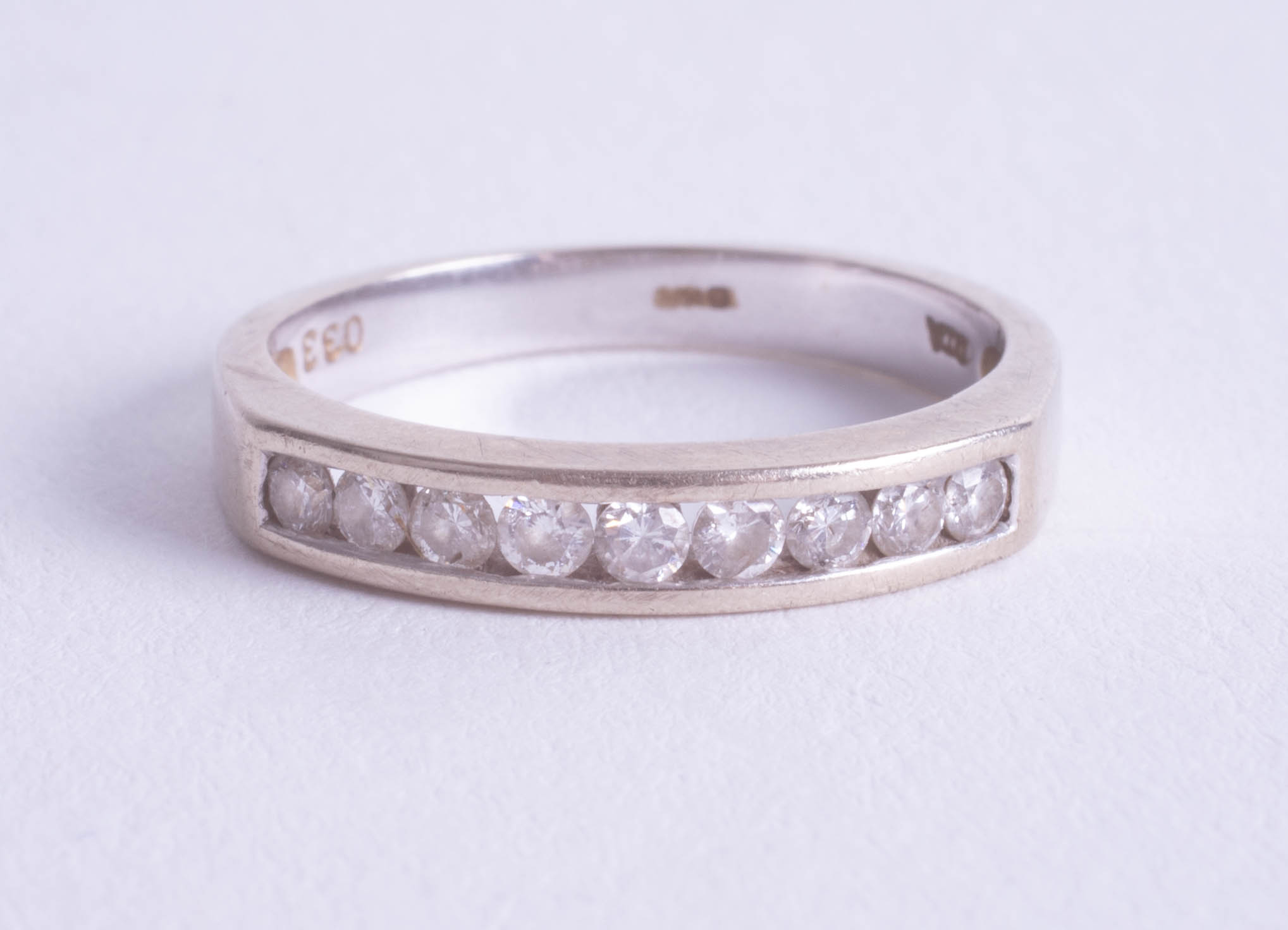 Lot 069 - A 18ct nine stone diamond half band eternity ring, approx 0.33ct, size M.