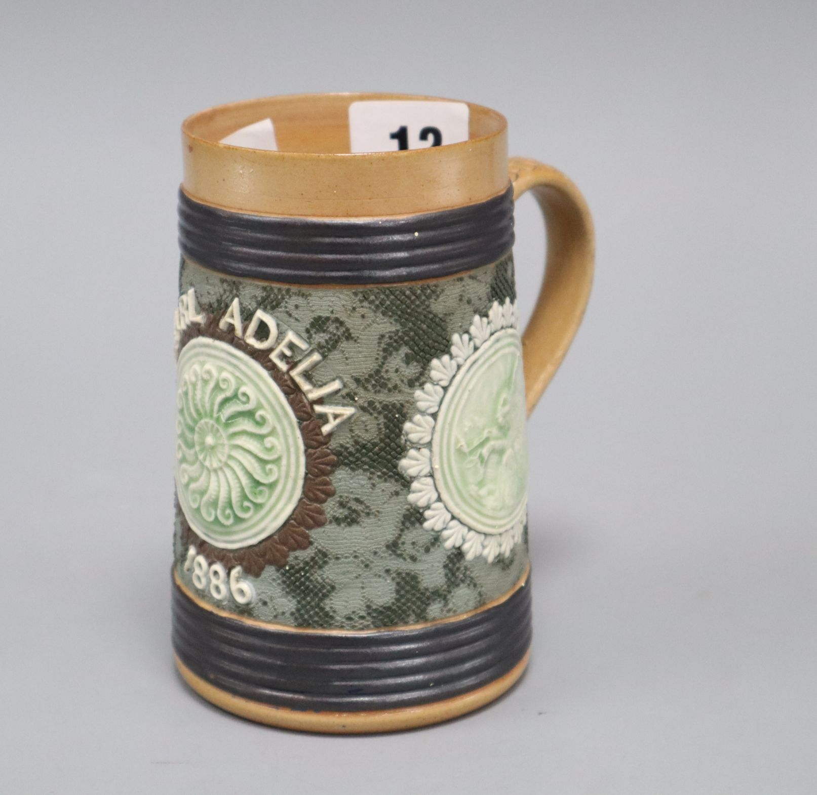 Lot 1012 - An unusual Doulton Lambeth 'tortoise & hare' mug, inscribed 'Pearl Adelia 1886', with green relief