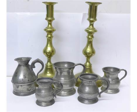 A pair of brass candlesticks, four measures and a 1 noggin measure in the form of a milk churn