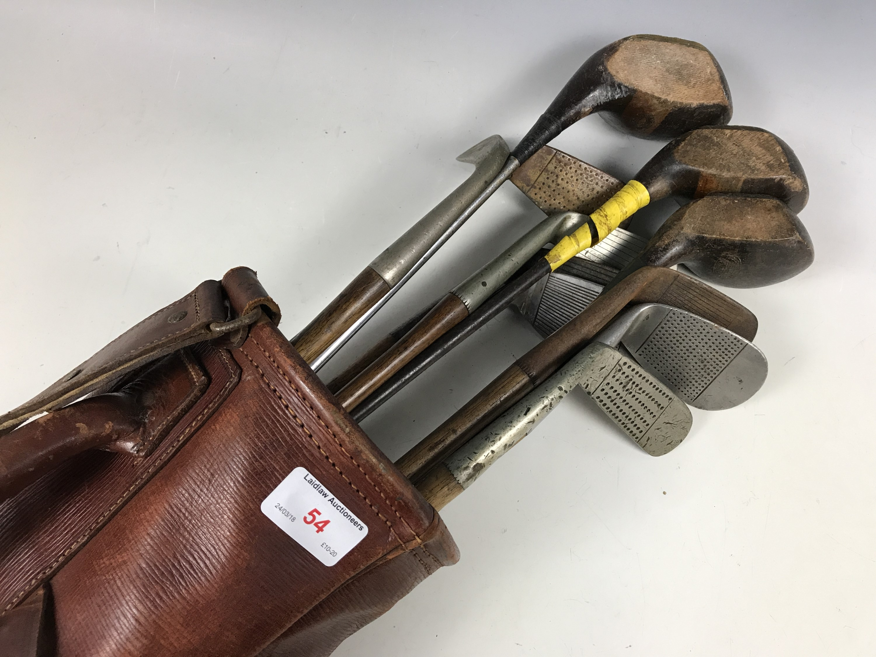 Lot 54 - A vintage canvas and hide golf bag with sundry hickory-shafted clubs by Saint Andrews, Seascale,