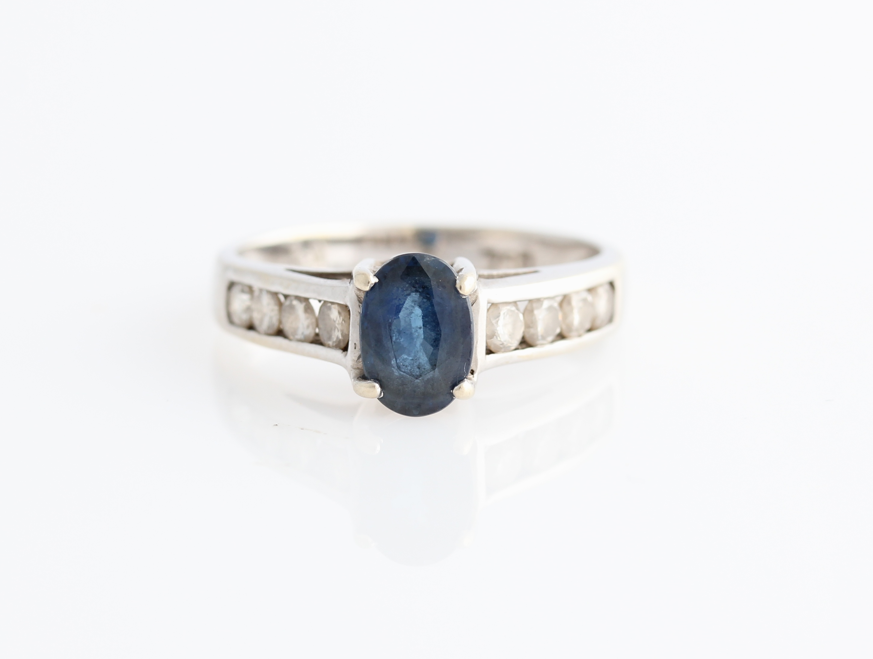 Lot 57 - A sapphire and diamond ring, set with an oval cut sapphire, measuring approx. 7x5mm, with each
