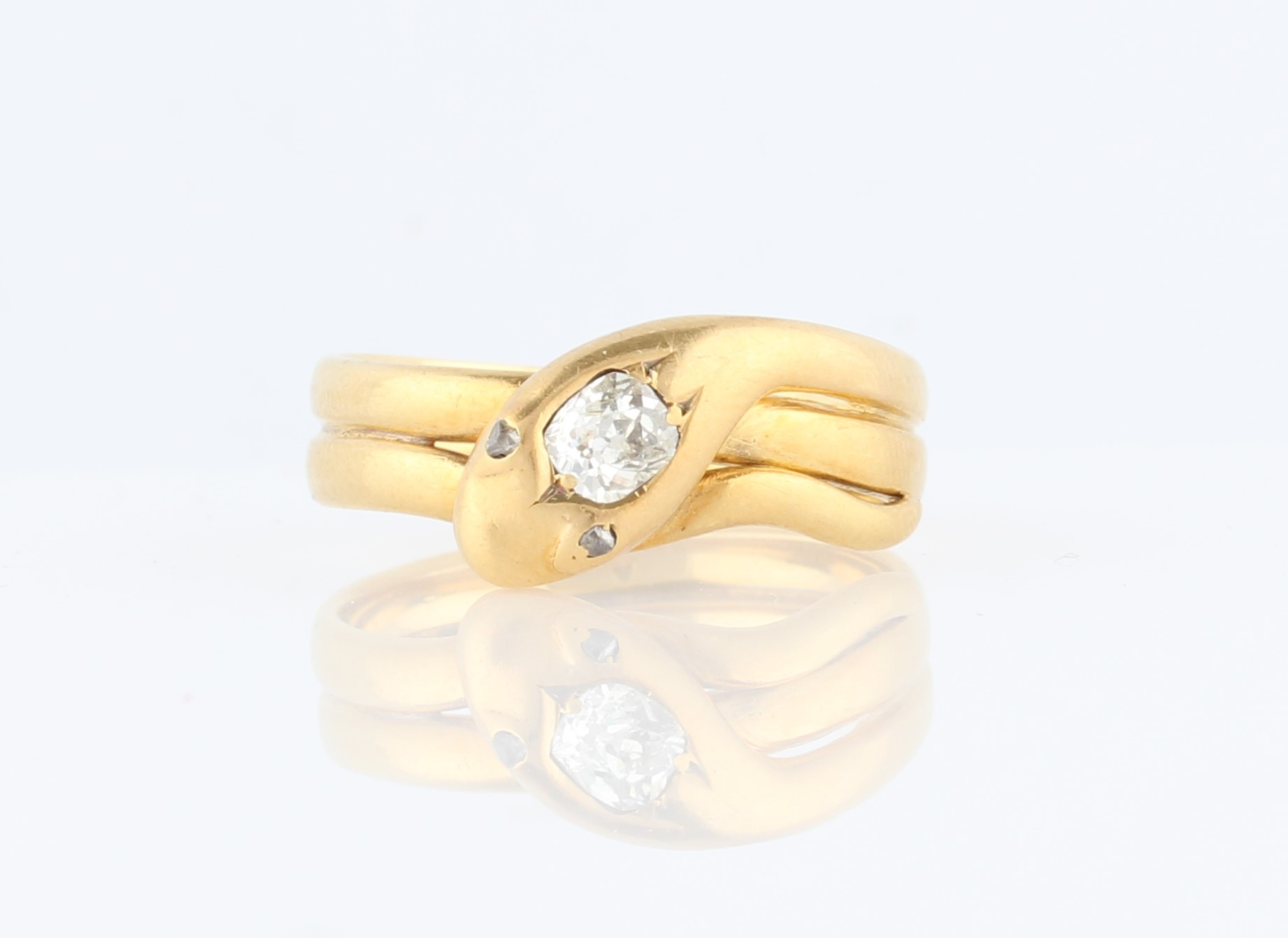 Lot 15 - A Victorian diamond set snake ring, the snake design set with an old mine cut diamond to head,