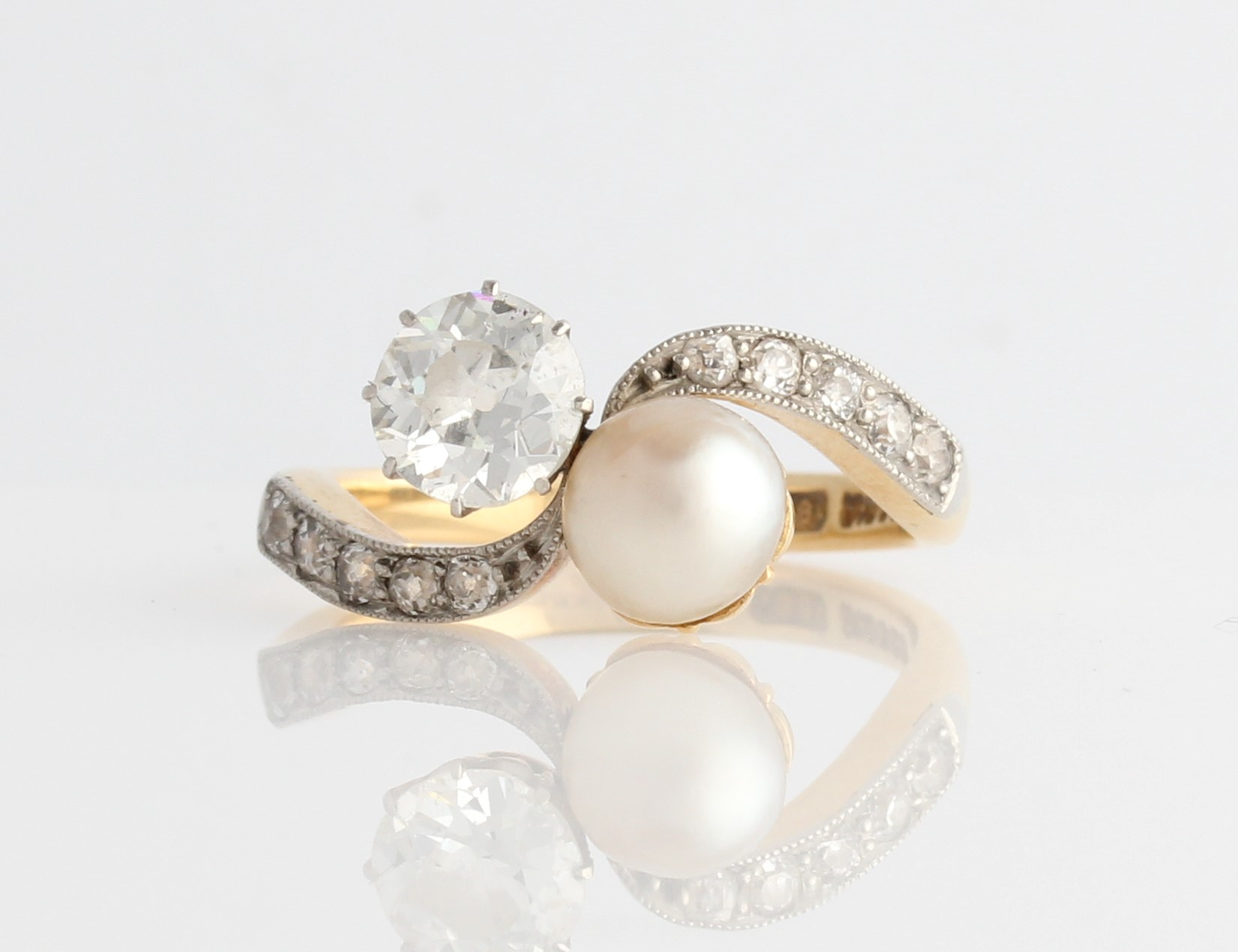 Lot 21 - A diamond and pearl ring, set principally with an Old European cut diamond, measuring approx. 0.