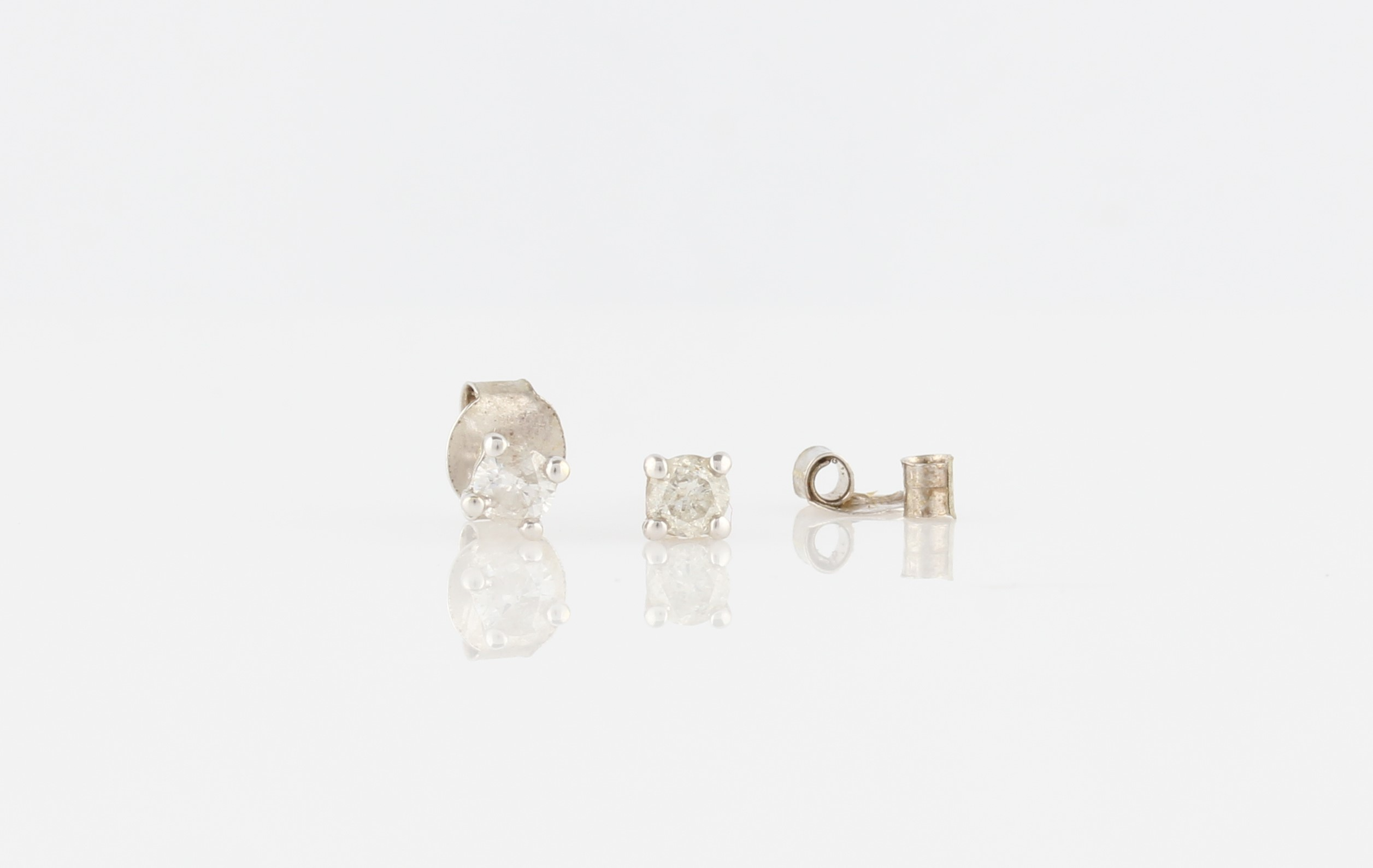 Lot 34 - A pair of diamond stud earrings, each set with a round brilliant cut diamond, measuring approx. 0.