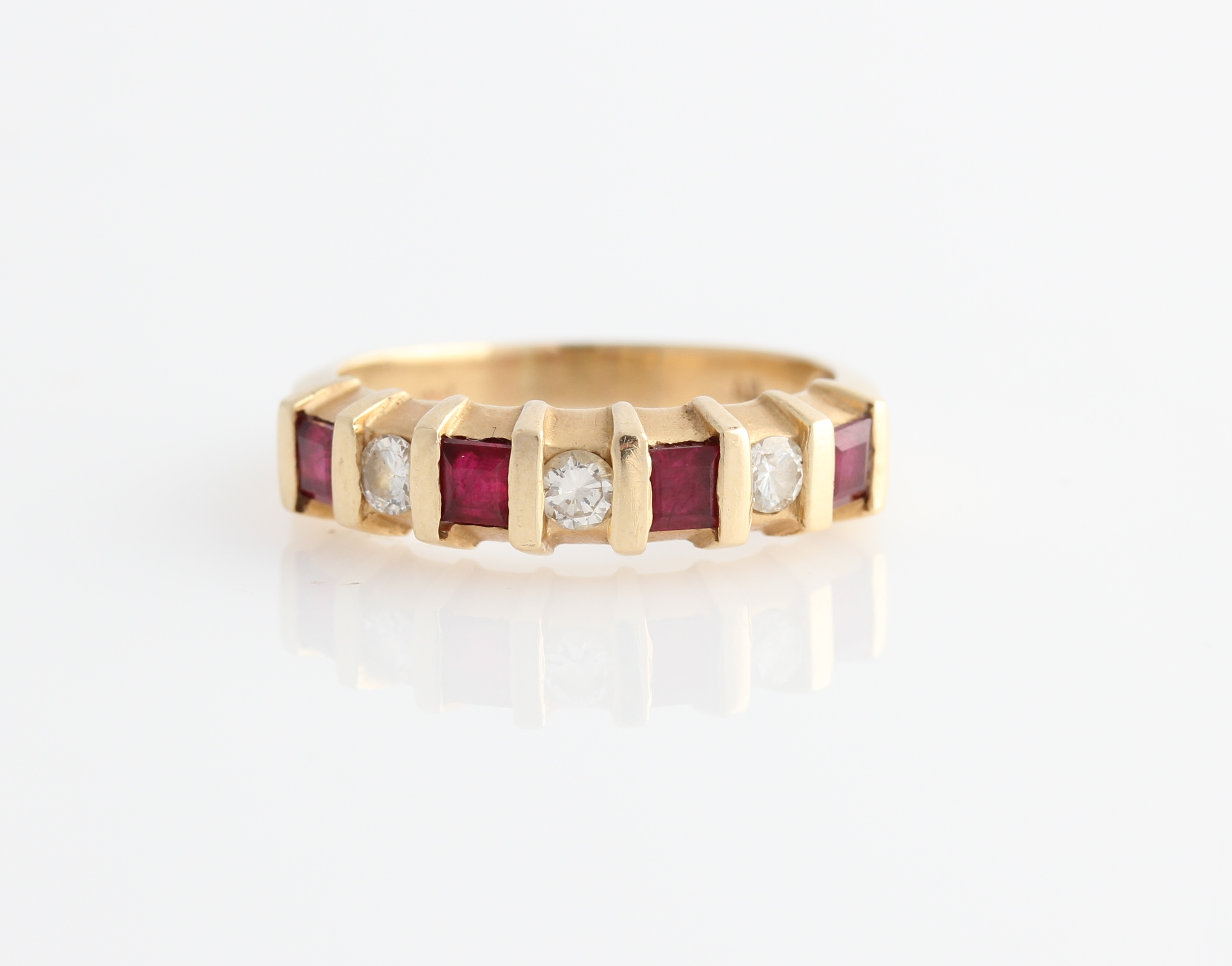 Lot 56 - A ruby and diamond seven stone ring, bar set alternately with four square cut rubies and three round