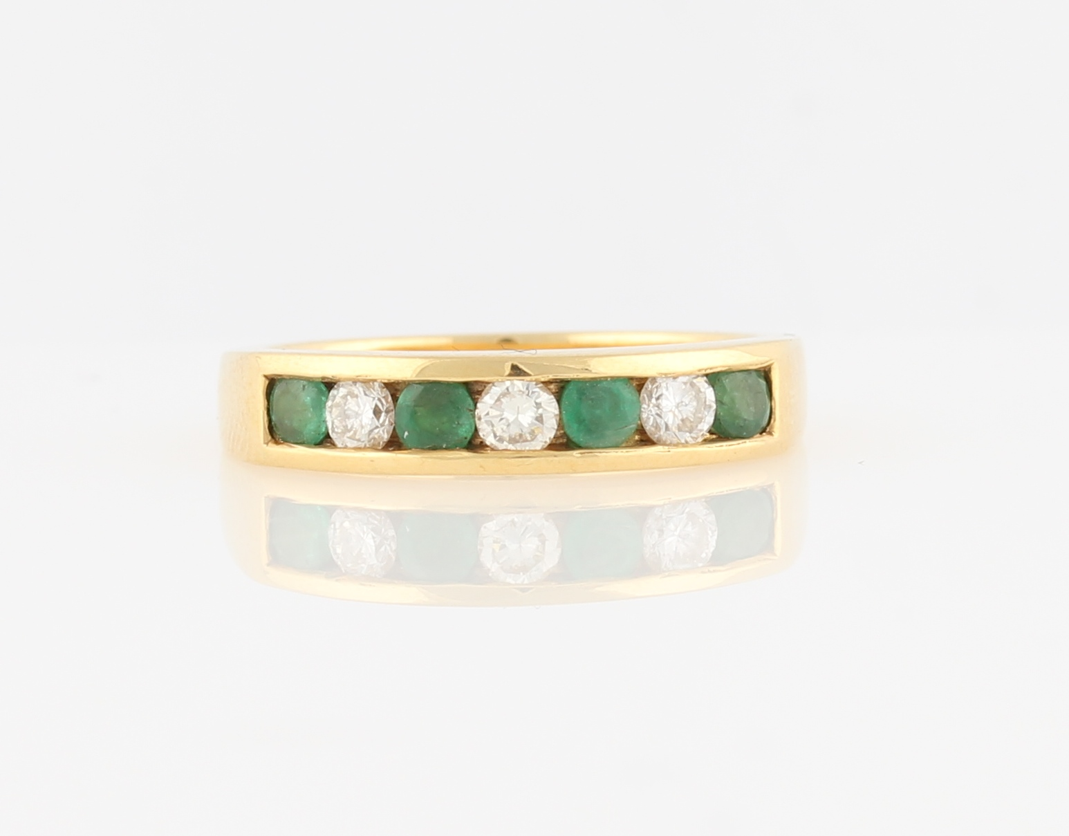 Lot 13 - A hallmarked 18ct yellow gold emerald and diamond half eternity ring, channel set with four round