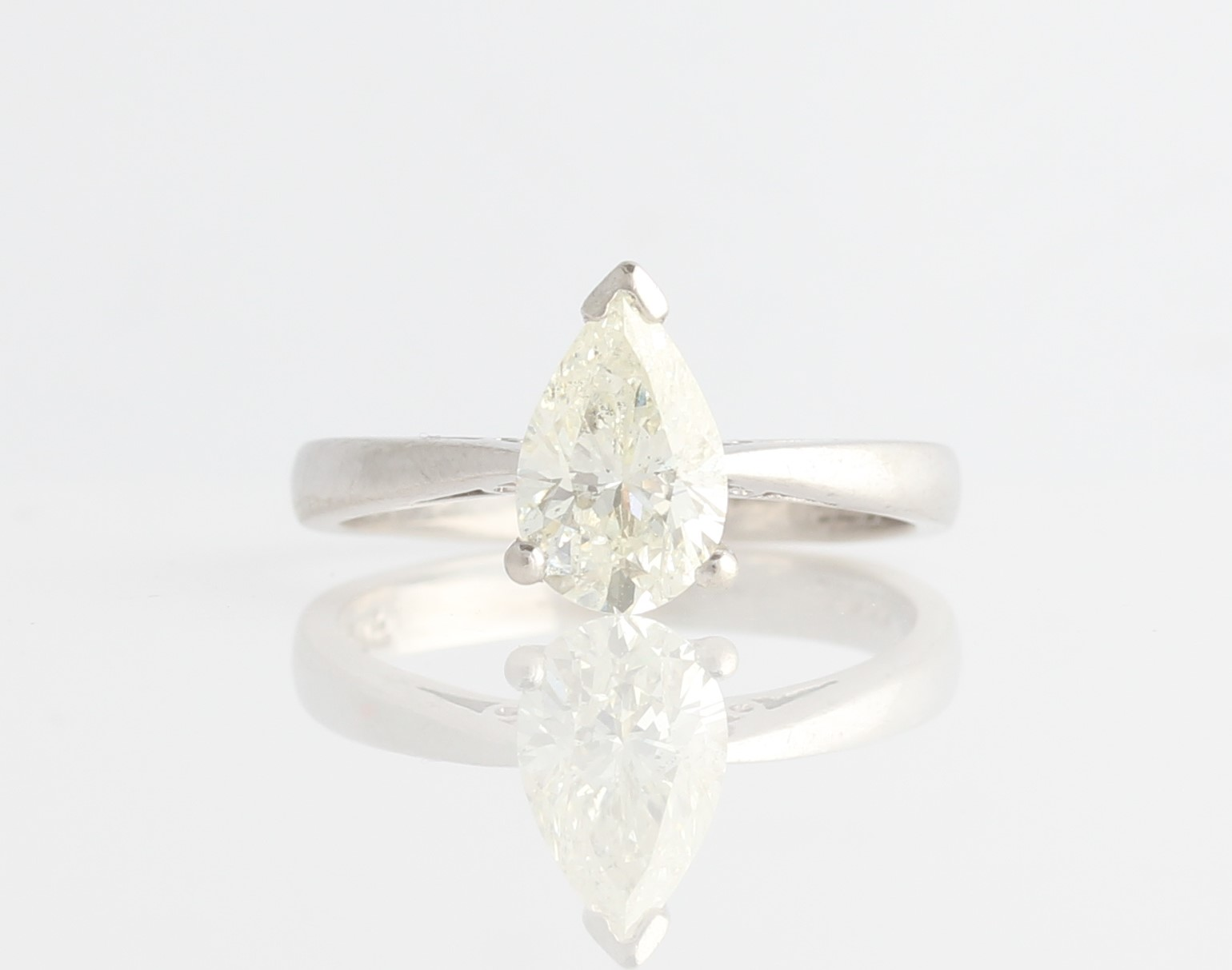 Lot 17 - A platinum diamond solitaire ring, set with a pear cut diamond, measuring approx. 1.28ct, hallmarked